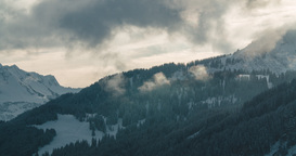 Time lapse of clouds rising from snowy forests during a sunset in Austrian Alps Footage