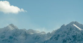 Time lapse of clouds flowing over snow covered mountain peaks in Austrian Alps Footage