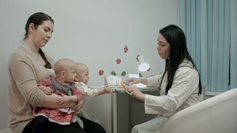 Female pediatrician doctor explain something to mother with newborn twins Footage