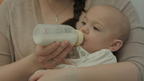 Cute baby eating milk from bottle Footage