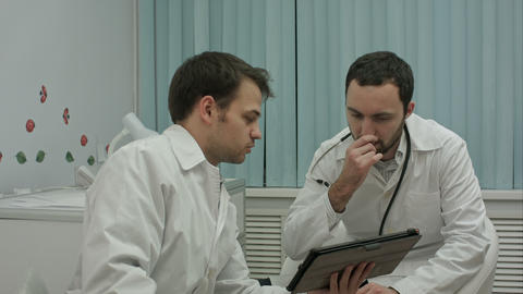 Male doctors watching on tablet pc and discussing results Footage