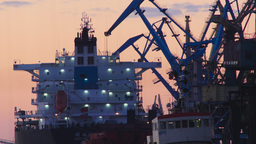 Silhouetted harbor cranes loading freight into a ship Footage
