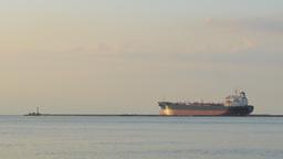 Empty bulk carrier leaving port behind a breakwater Footage