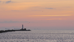 Breakwater with a lighthouse during sunset Footage