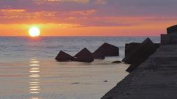 Sun setting behind a bulk carrier over a calm sea Footage