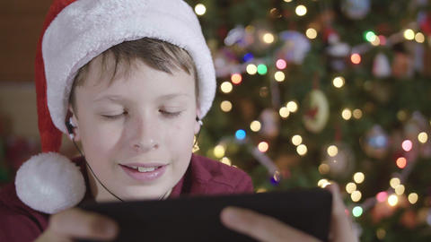 Front View of Young Boy Wearing Santa Hat and Headphones Browsing Internet on Ta Footage