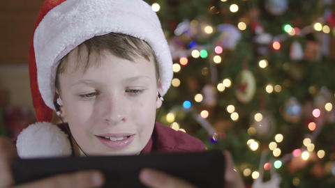 Front View of Young Boy Wearing Santa Hat and Headphones Smiling at Video on Tab Footage