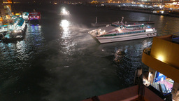 Ferry traffic night pier, ship turn on powerful spotlight while approaching Footage