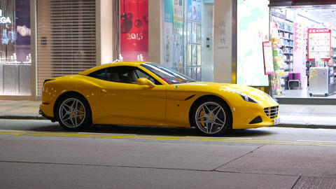 Yellow Ferrari California car parked on night street, urban view Footage