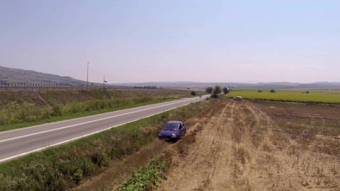 Blue car going on a country road next to the main road 1 Footage