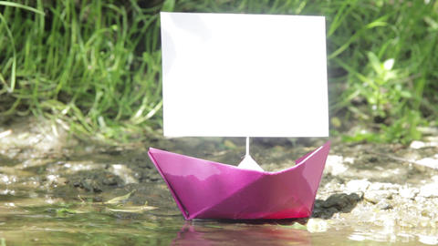 Purple paper boat that ran aground on the rocky shore of the river 229 Footage