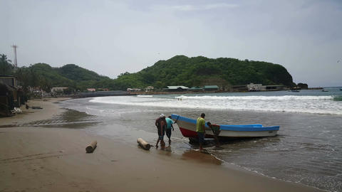 Fishermen pushing boat ashore Footage