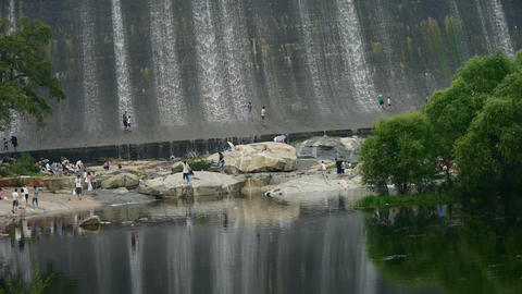 People are playing under dam,Waterfall texture Footage