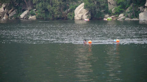 People swimming in lake with floats buoy,relying on... Stock Video Footage