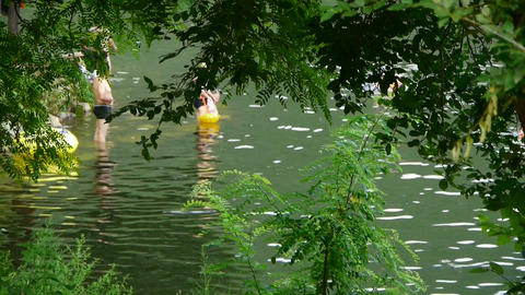 People swimming in lake,relying on Castle Peak,leaves shade Stock Video Footage