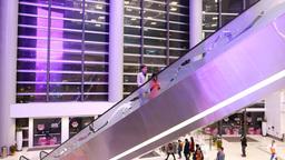 Steel escalator against empty mall atrium and illumination behind windows Footage