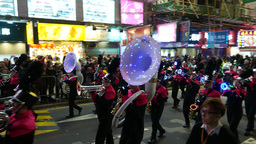 Wind instruments orchestra marching on night street, parade procession Footage