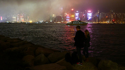 Night Hong Kong shore, couple with camera watching beautiful cityscape Footage