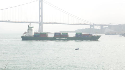 Container ship against suspension bridge, telephoto tracking shot, fog haze view Footage