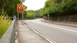 Empty twisted road in woodland mountain, reduce speed sign Footage
