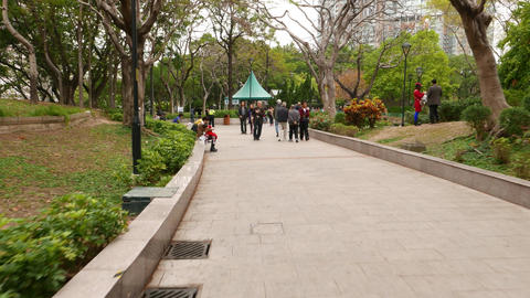 Pathway in Tuen Mun Park, Hong Kong suburb. People rest and walk in the garden Footage
