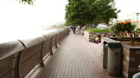 Walking through Tuen Mun promenade, people resting at sea-front park Footage