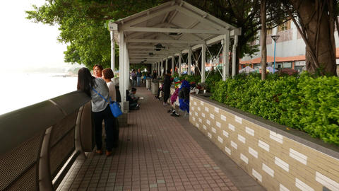 People resting in covered sea-front promenade at daytime, Tuen Mun town Footage