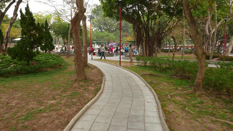 Moving on walkway in park, to crowdy barbecue zone Footage