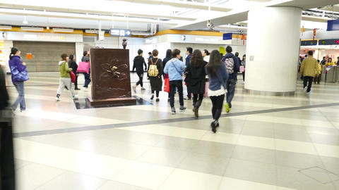 People walking in bright metro station hall, camera move close to art sculpture Footage