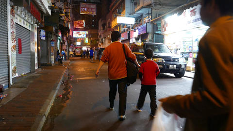 Chinese man walking with son at night street, chasing camera behind the pair Footage