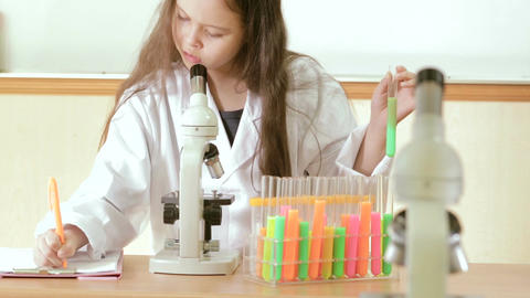 Child scientist holding test tube looking through microscope and making notes Footage