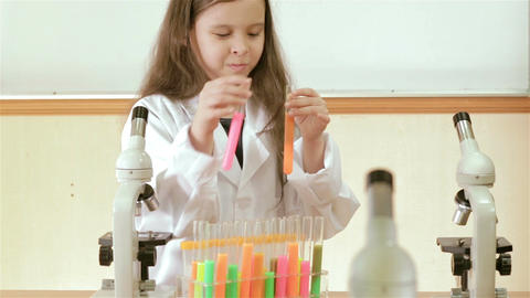 Child scientist mixing test tubes and smiling at camera Footage