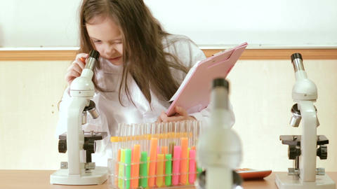Child scientist recording lab results in file Footage