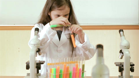 Young girl mixing liquids in test tubes and smiling at camera Footage