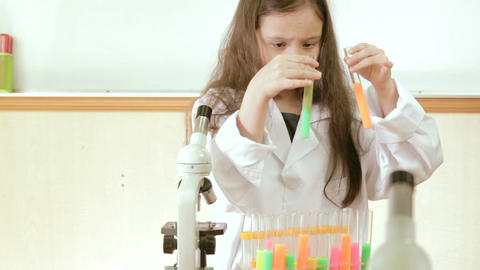 Young scientist mixing liquids in test tubes and noting Footage