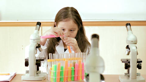 Young scientist sitting in lab mixing liquids in test tubes Footage
