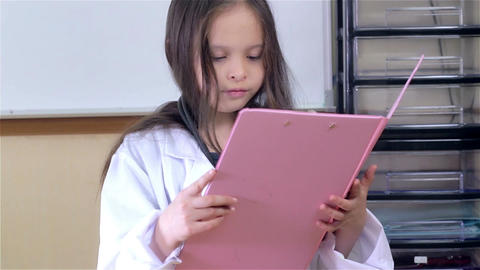 Child doctor inspecting file Footage