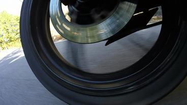 Rear wheel view. Bike is around the corner Footage