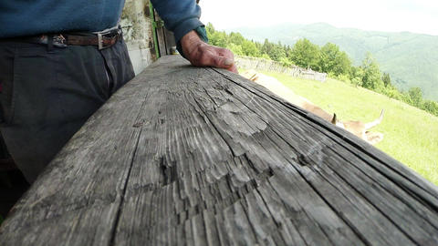 the old man's hand rests on the broad wooden railing close up Footage