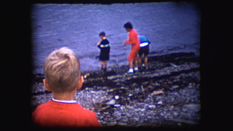 Vintage 8mm footage of boys playing on a shore Footage
