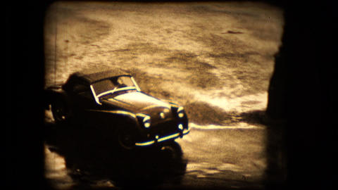 A TR2 Triumph sports car pulls away from the camera Footage