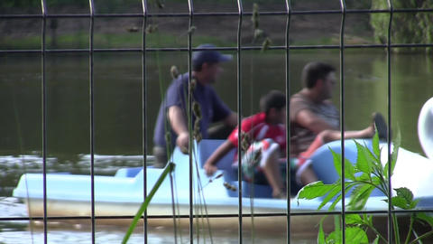 People who give boats on a lake behind a metal fence 2 Footage