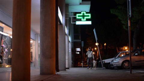Man talking on cell phone while is walking in front of a pharmacy at night 01 Footage