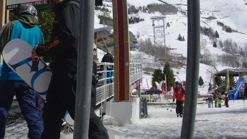 Skiers who climb up on a gangway to the central station of the cable car that wi Footage