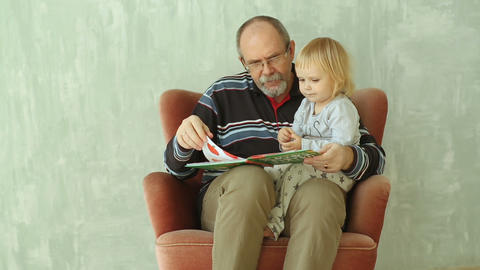 Grandfather read a book with little granddaughter Footage
