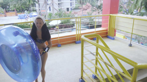 Girl with rubber ring going to ride on waterpark slide Footage