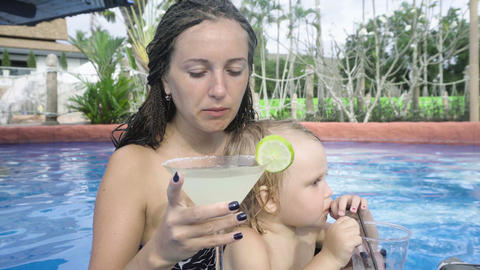 Young girl with little child sitting in swimming pool bar and drinks cocktail Footage