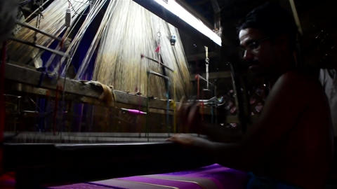 Mid shot of an Indian weaver weaving manually Filmmaterial
