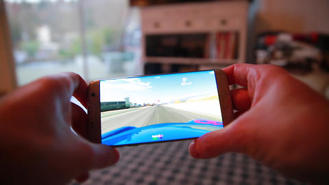 Man Playing A Video Game On His Smartphone At Home Footage