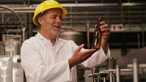 Factory worker inspecting a glass bottle at bottling plant Live Action